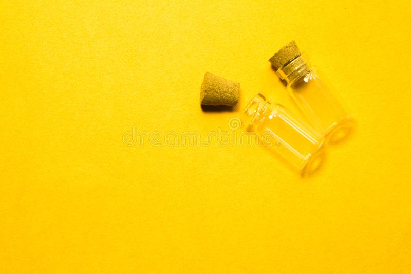 Empty little bottles with cork stopper isolated on yellow. transparent containers. test tubes. copy space. Empty little bottles with cork stopper isolated on royalty free stock image