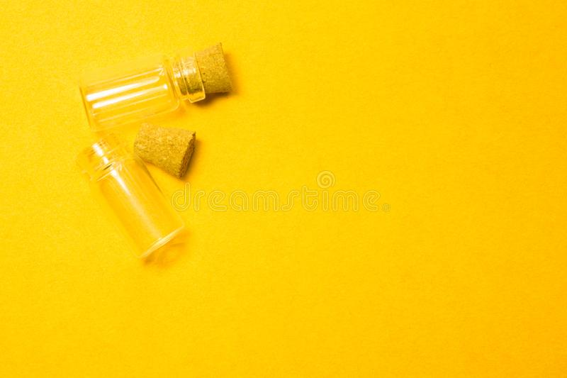 Empty little bottles with cork stopper isolated on yellow. transparent containers. test tubes. copy space. Empty little bottles with cork stopper isolated on stock image