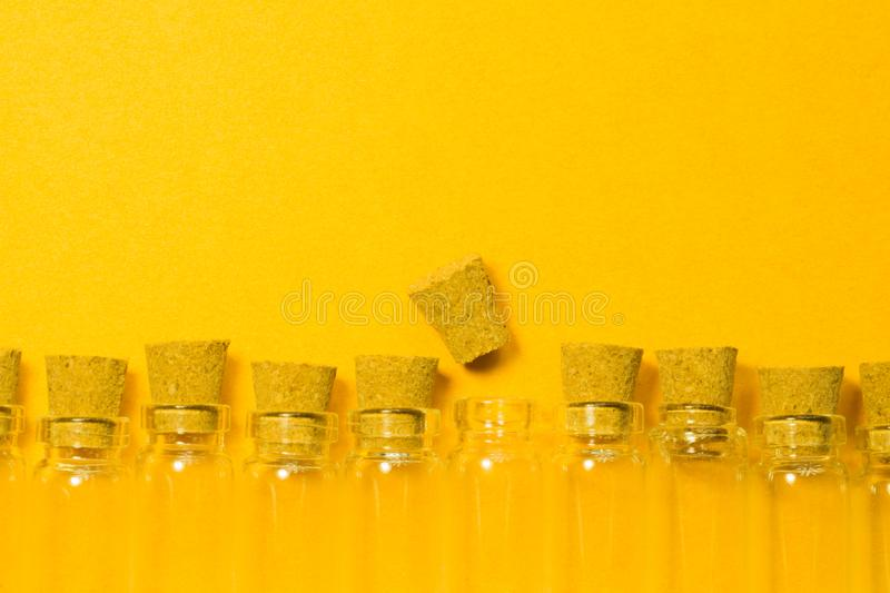 Empty little bottles with cork stopper isolated on yellow. transparent containers. test tubes. Empty little bottles with cork stopper isolated on yellow. glass royalty free stock images