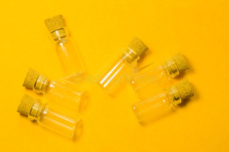Empty little bottles with cork stopper isolated on yellow. transparent containers. test tubes. Empty little bottles with cork stopper isolated on yellow. glass stock image