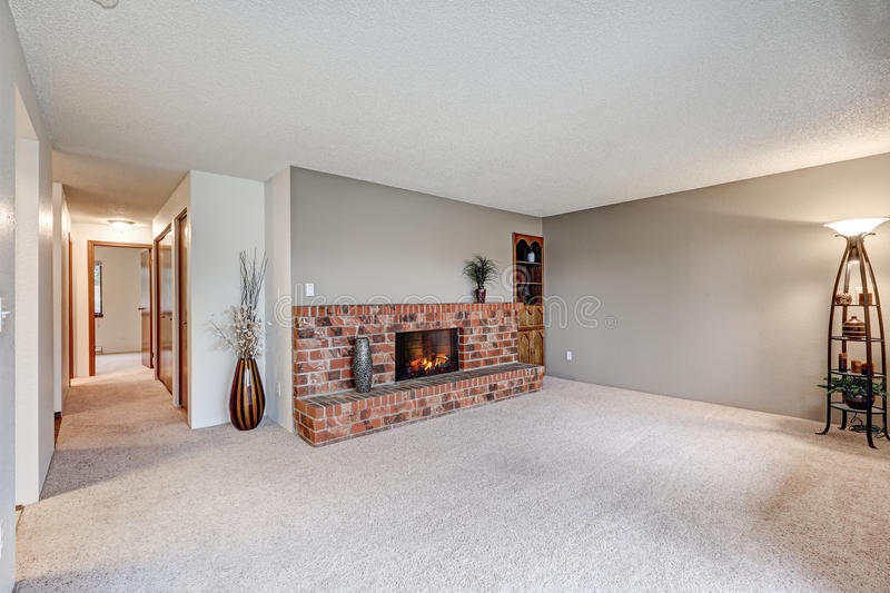 Empty living room features grey walls. Empty living room next to hallway features grey walls, carpet floor and red brick fireplace. Northwest, USA royalty free stock photos