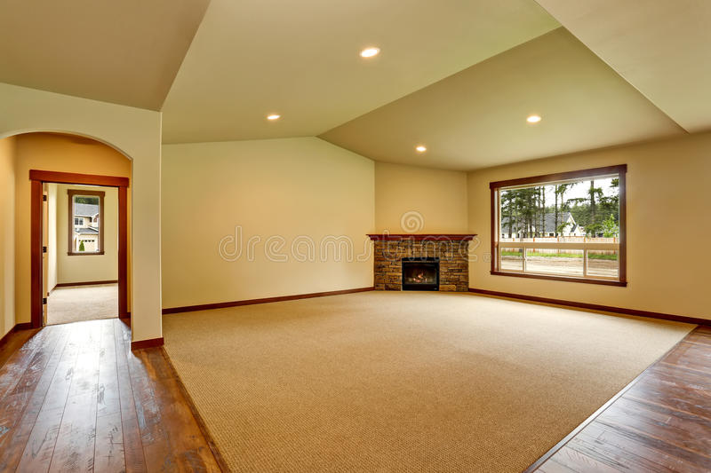 Empty living room with fireplace. Connected to kitchen area. stock image