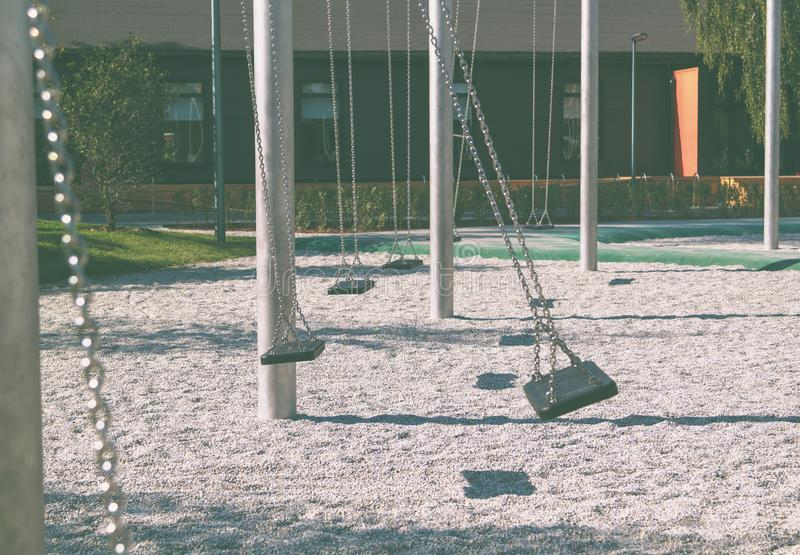 Empty lonely swings in a modern park. Playground, old, abandoned, set, toy, swingset, chain, white, young, background, sad, fun, grass, equipment, youth, child stock photos