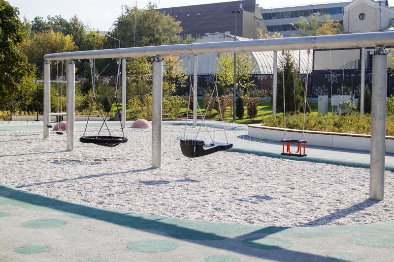 Empty lonely swings in a modern park. Playground, old, abandoned, set, toy, swingset, chain, white, young, background, sad, fun, grass, equipment, youth, child stock photo