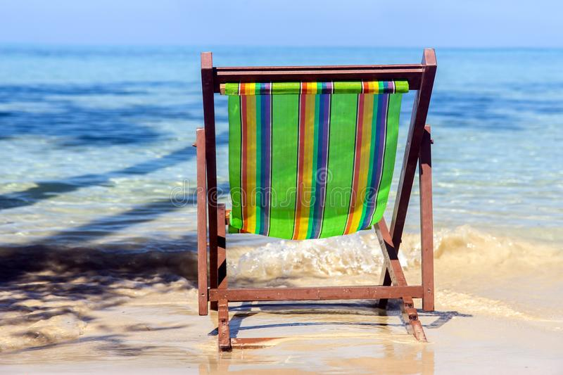 Empty lounger on the sea beach. Colorful chair stands abandoned on a sunny seashore. Vacation on a tropical island royalty free stock photography