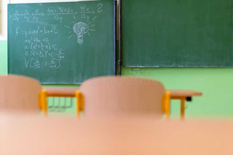 Empty Mathematics classroom with school desks, chairs and blackboard. Education concept stock photos