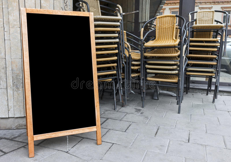 Empty menu board and stacked cafe chairs royalty free stock image