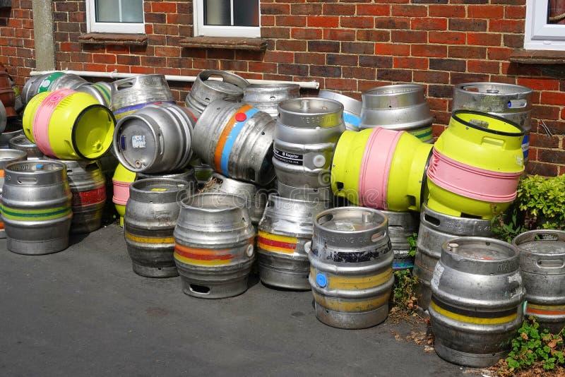 Empty metal beer barrels or kegs. Several steel beer barrels or kegs awaiting collection outside a pub in England stock image