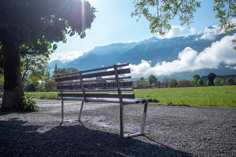Empty metal bench in public park at Interlaken with mountain and clear blue sky background stock photo