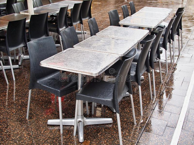 Empty Oiutdoor Cafe Tables in the Rain. Empty metal cafe coffee shop tables, wet in the rain. An inclement weather day, bad for an outdoor business stock photo
