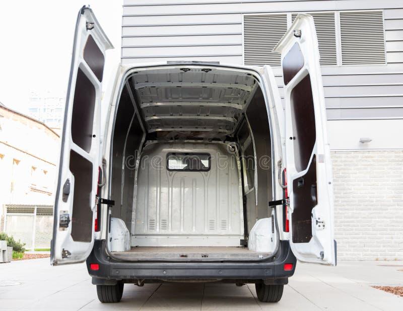 Empty minivan car with open doors on city parking. Freight transportation, logistics, transport and vehicle concept - white empty minivan car with open doors on stock images
