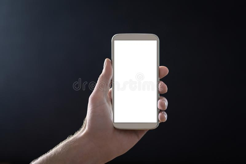 Empty mobile phone screen with dark black background in shadow at night. Hand holding smartphone with blank white display. stock photos
