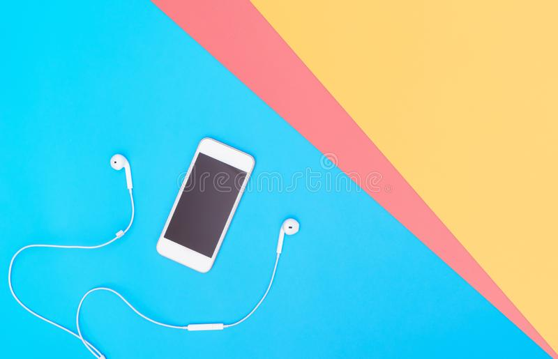 Mobile phone screen with Music earphone on blue copy space. Empty Mobile phone screen with Music earphone on blue copy space for poster and text stock photo