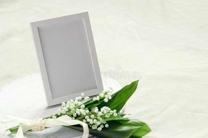 mock up photo frame and bouquet of lilies of the valley royalty free stock image