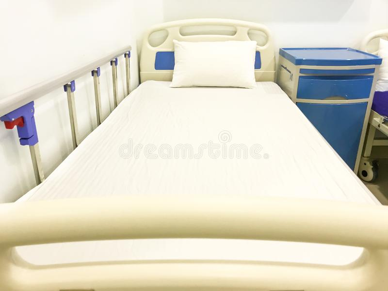 Empty modern hospital or clinical comfortable clean white bed for patient recovery stock photo