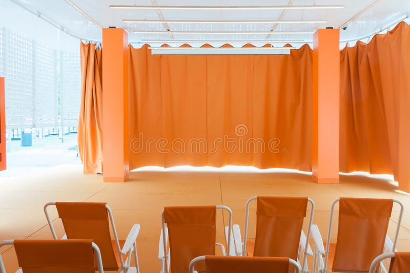 Empty modern interior assembly room with red curtain and seats in sun light outside royalty free stock photos