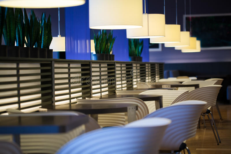 Empty modern restaurant interior. With chairs, tables and hanging lamps royalty free stock images