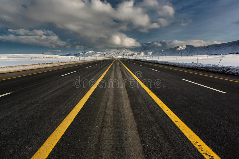 Empty motorway. And clouds meet in vanishing point royalty free stock images