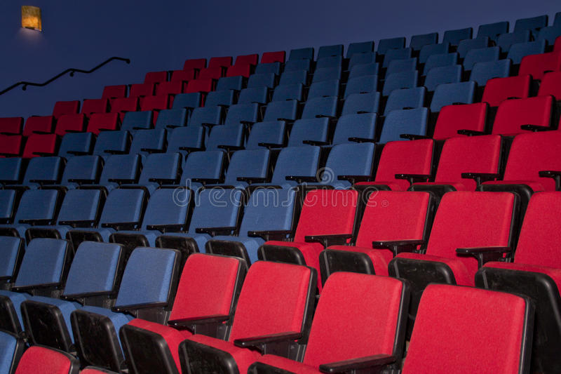 Empty Movie Theater Seats. Colorful and comfortable seating at indoor movie theatre stock photo