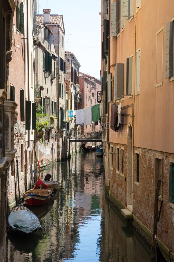 Narrow canal in Venice with moored gondolas and facades of old houses stock photo