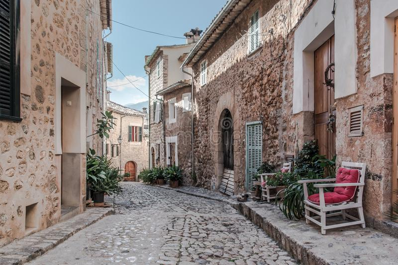 Empty narrow cobbled street in small spanish village with typical houses. On both sides royalty free stock photography