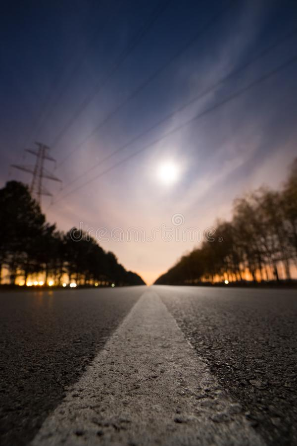Empty night asphalt road, bright full moon behind clouds and city light behind two rows of trees on both side of road royalty free stock images