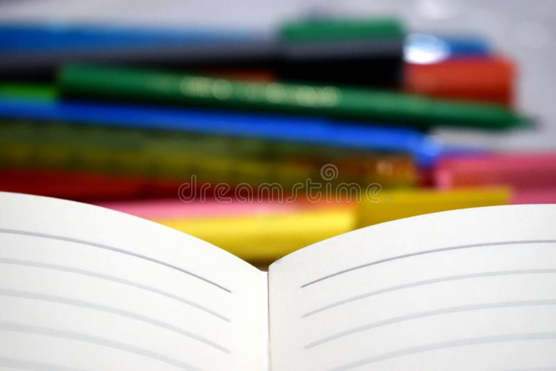 Empty note book with blurred   colour soft tip pens. Empty note book with blurred  colour soft tip pens in the background royalty free stock images