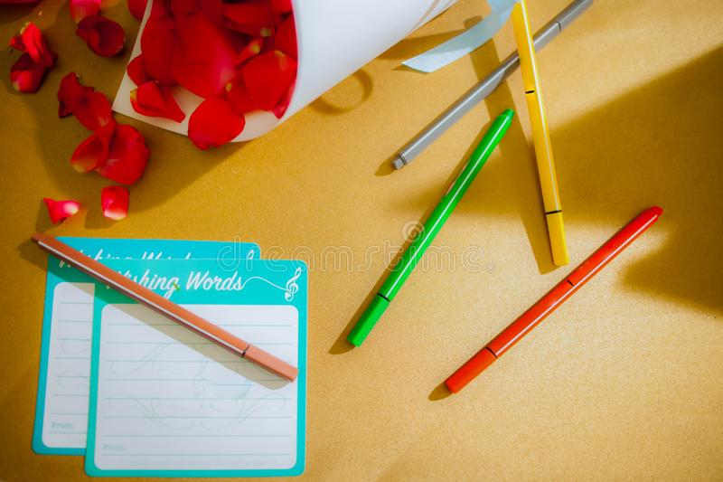 Empty note pad for writing and colorful pens with rose. Put on the brown table royalty free stock photo