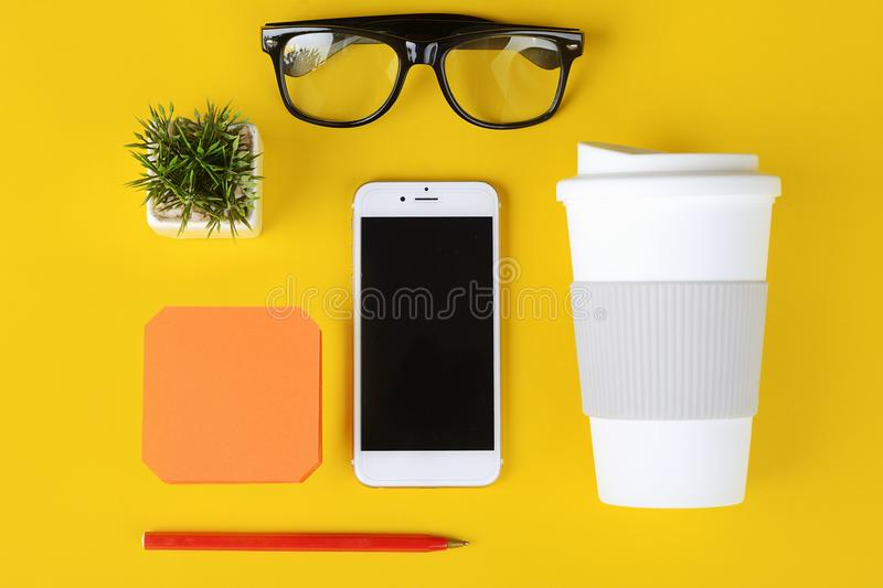 Empty note paper with plastic cup of coffee, pen, phone and glasses royalty free stock image