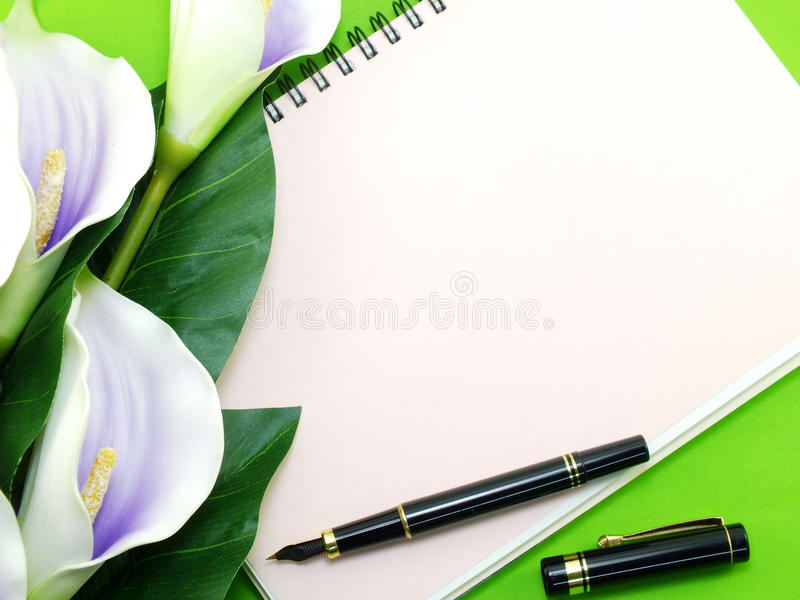 Empty notebook and beautiful calla artificial violet flowers bouquet. Open notebook and beautiful calla artificial violet flowers bouquet royalty free stock photo
