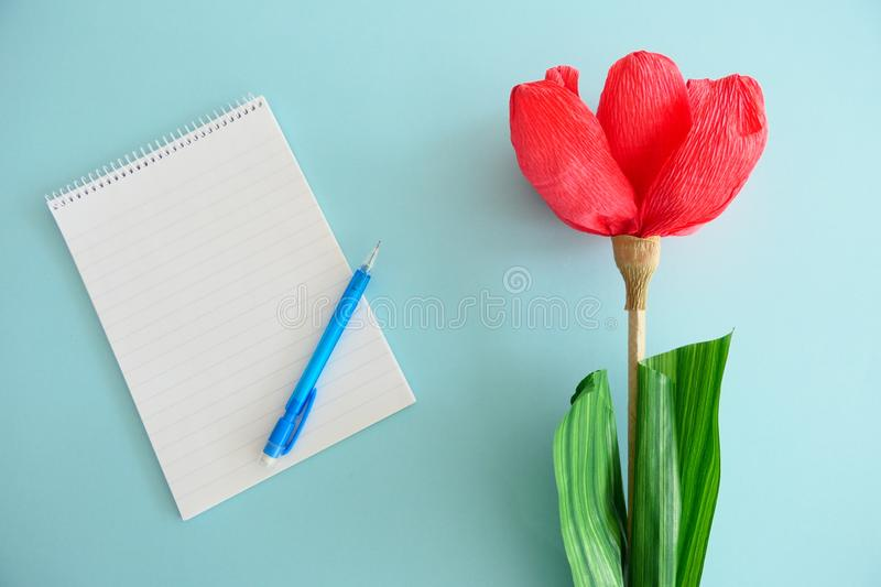 Empty Notebook, Blue Pen and a Red Paper Flower  on a Light Blue Background. Empty Notebook, Blue Pen and a Red Paper Flower  on a Blue Background stock photography