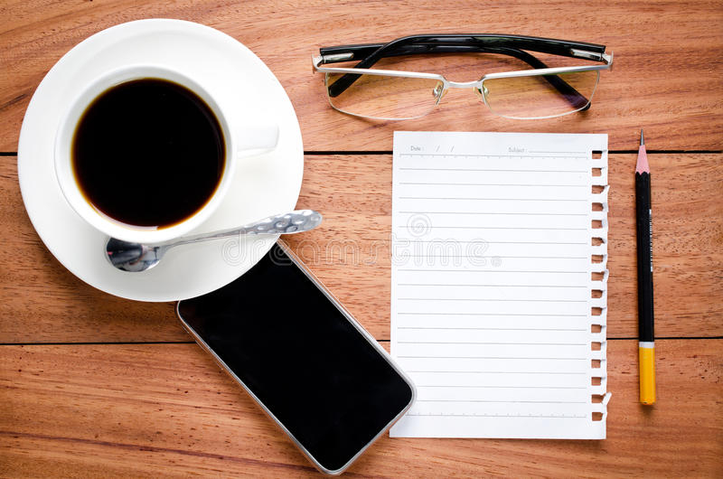 Empty notebook and a cup of coffee. On the wooden desk background royalty free stock photography