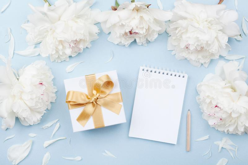 Empty notebook and gift or present box decorated white peony flowers on pastel table top view. Flat lay composition for birthday. Or wedding stock images
