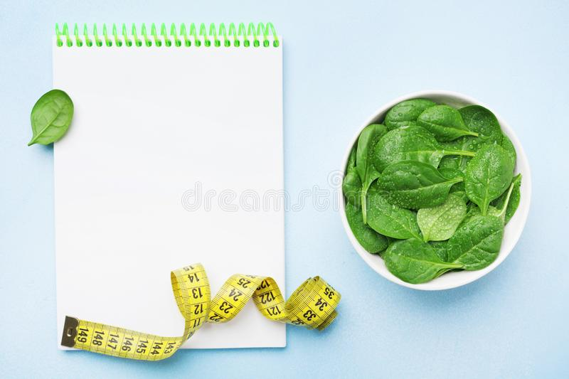 Empty notebook, green spinach leaves and tape measure on blue table top view. Diet and healthy food concept. Empty notebook, green spinach leaves and tape royalty free stock image