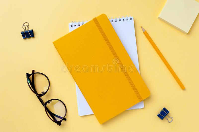 Empty notebook and office stationery yellow background. Office stationery equipment. Empty notebook and glasses on yellow background. Bright colorful workplace stock photos