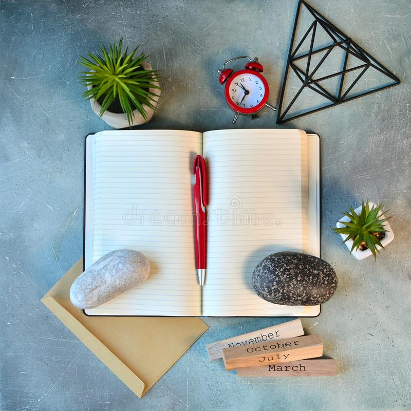 Empty notebook page, clock, flowers, stones and other decor. Flat lay.  royalty free stock photo