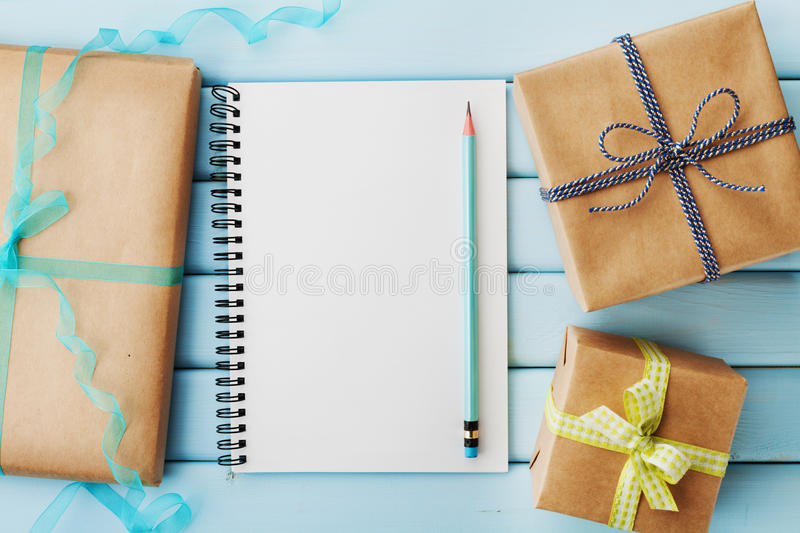 Empty notebook, pencil and gift or present box packed in kraft paper on blue wooden table. Top view royalty free stock photos