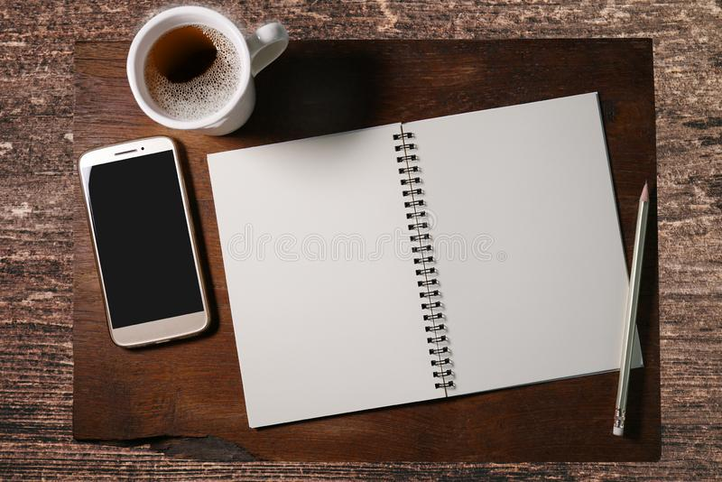 Empty notebook with pencil, smartphone and white cup of coffee on brown wooden table. stock photo