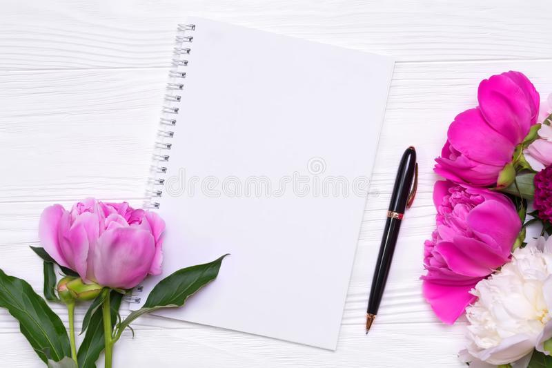 Empty notebook with place for text and peonies flowers on a white background. Empty notebook with place for text and peonies flowers on a white wooden background stock photography