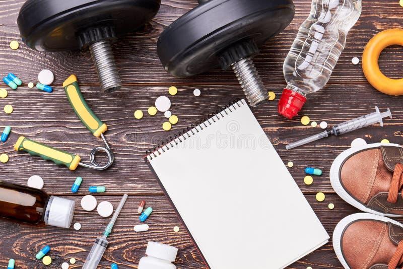 Empty notebook, syringes, pills, dumbbells. royalty free stock photos