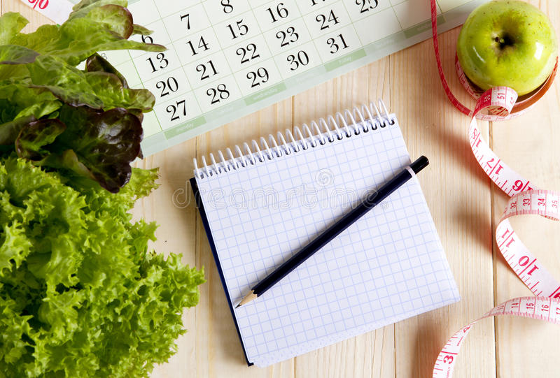 Empty notebook with vegetable salad and apple. Calendar on wooden table royalty free stock photography
