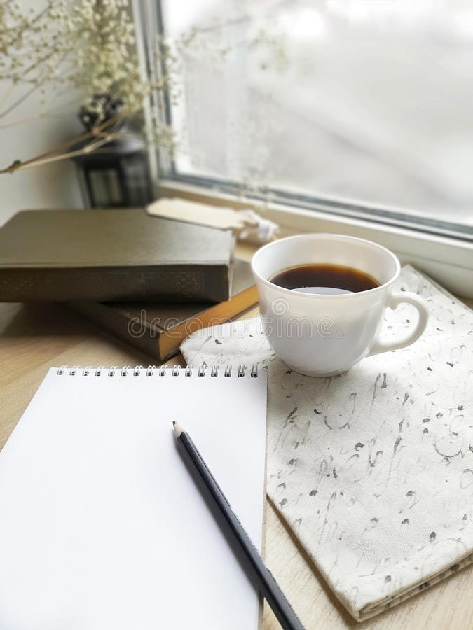 Empty notepad, coffee cup and books on  wooden windowsill. royalty free stock photo
