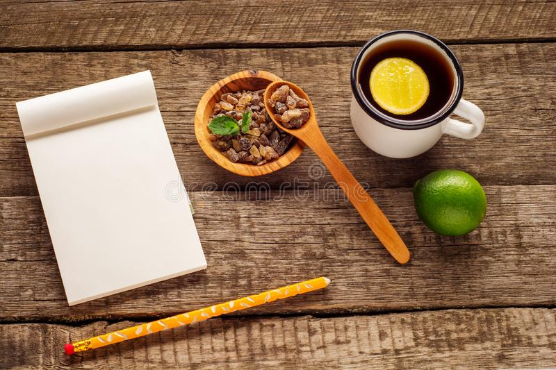 Empty notepad and pencil on the wooden table. Cup of tea, lime and sugar on rustic background. Empty notepad and pencil on the wooden table. Cup of tea, lime stock image