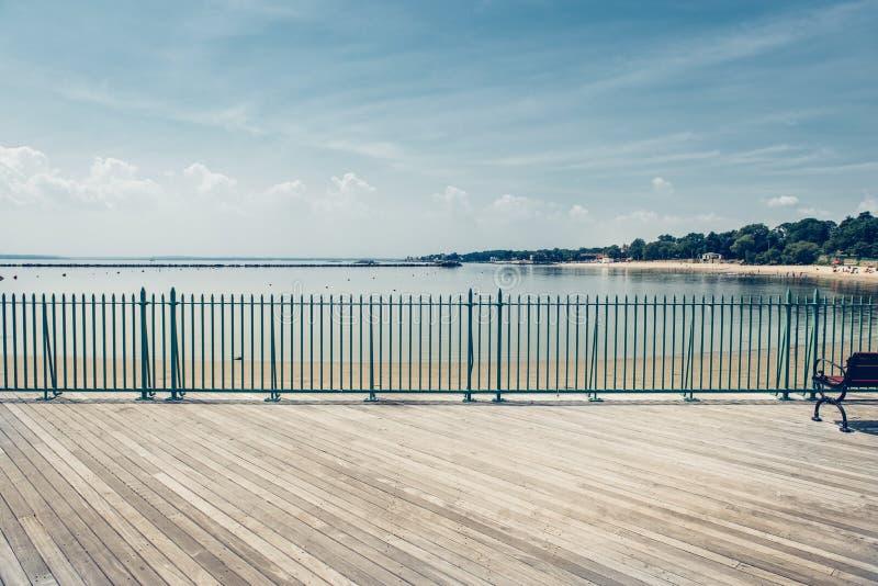 Empty ocean beach boardwalk pier at hot summer day against blue sky. ÑŽ royalty free stock photography
