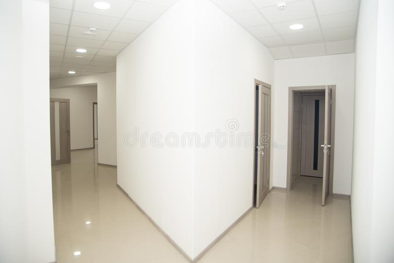 Empty office corridor with many doors of light wood.  royalty free stock photography