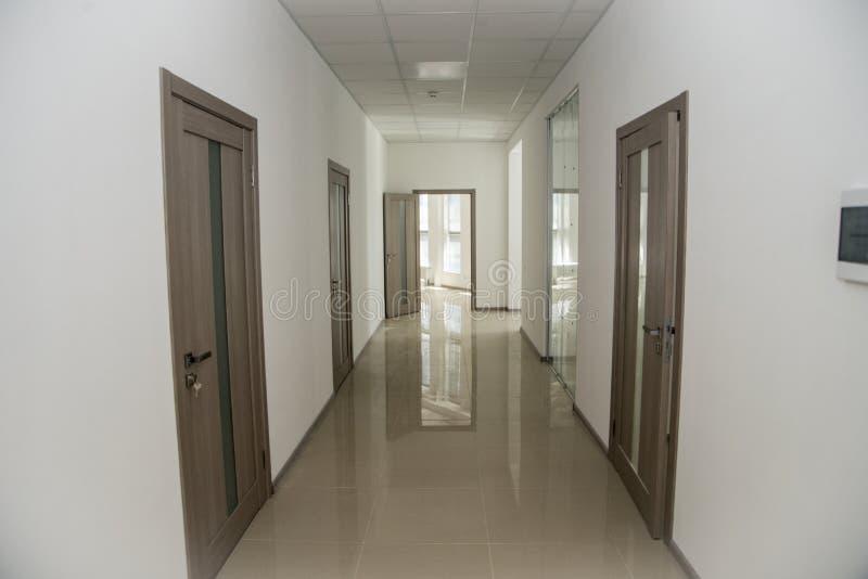 Empty office corridor with many doors of light wood.  stock photography