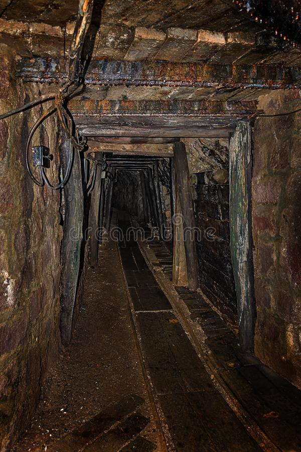 Empty old abandoned mine shaft with wooden timbering and rusty railway royalty free stock images