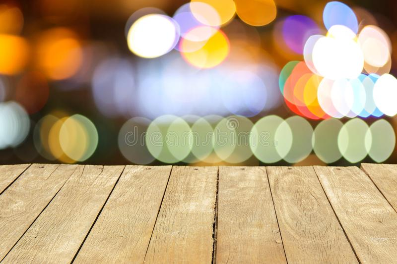 Empty old painted color wooden table or plank with bokeh of light from road or street with city tower on background. royalty free stock photos