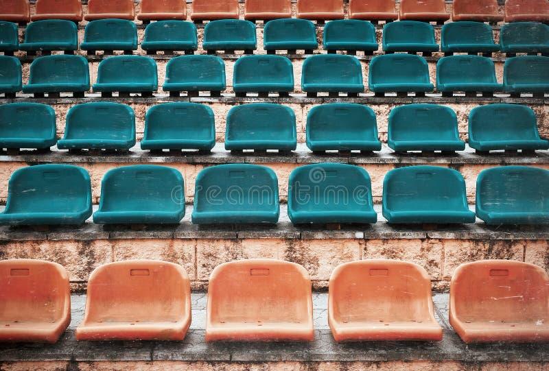 Empty old plastic seats at stadium, open door sports arena. Vintage photo royalty free stock image
