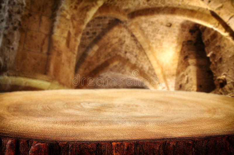 Empty old table in front of ancient knight stone tower. Useful for product display montage. royalty free stock image